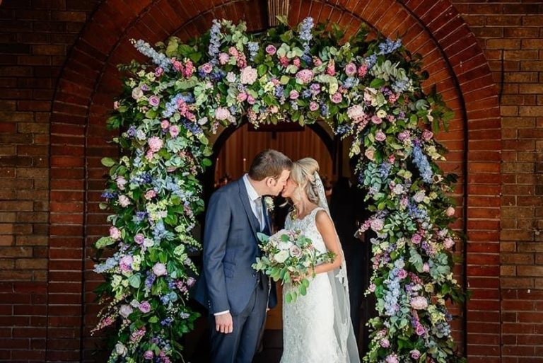 Bride and groom under a floral arch